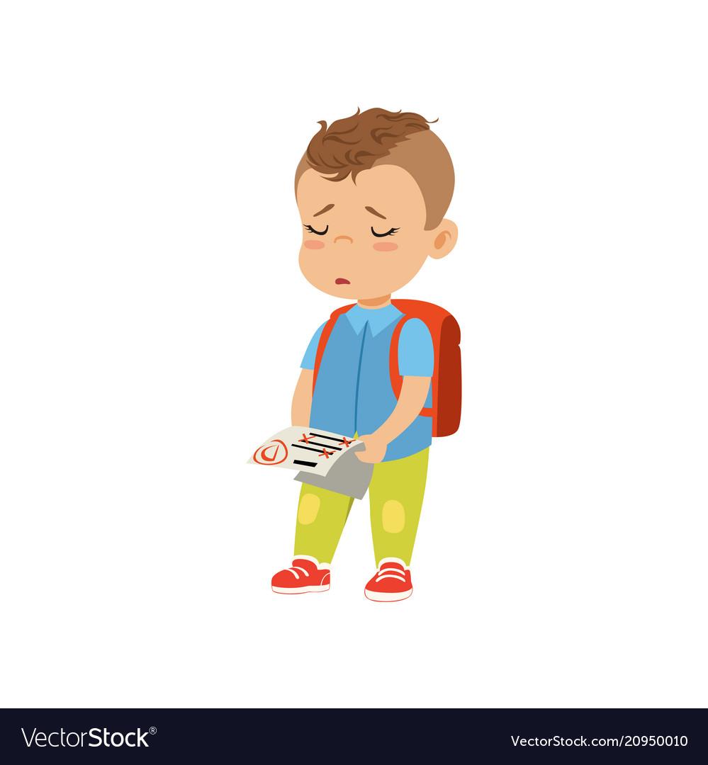 Sad little schoolboy holding test paper with bad