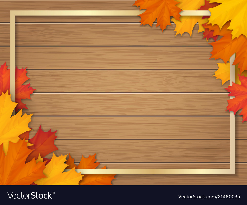 Autumn leaves and frame on wooden background