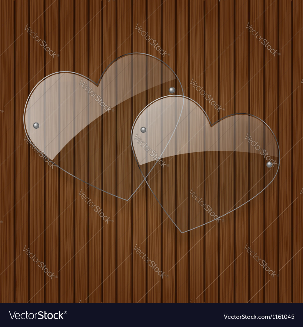 Two glass hearts over wooden background