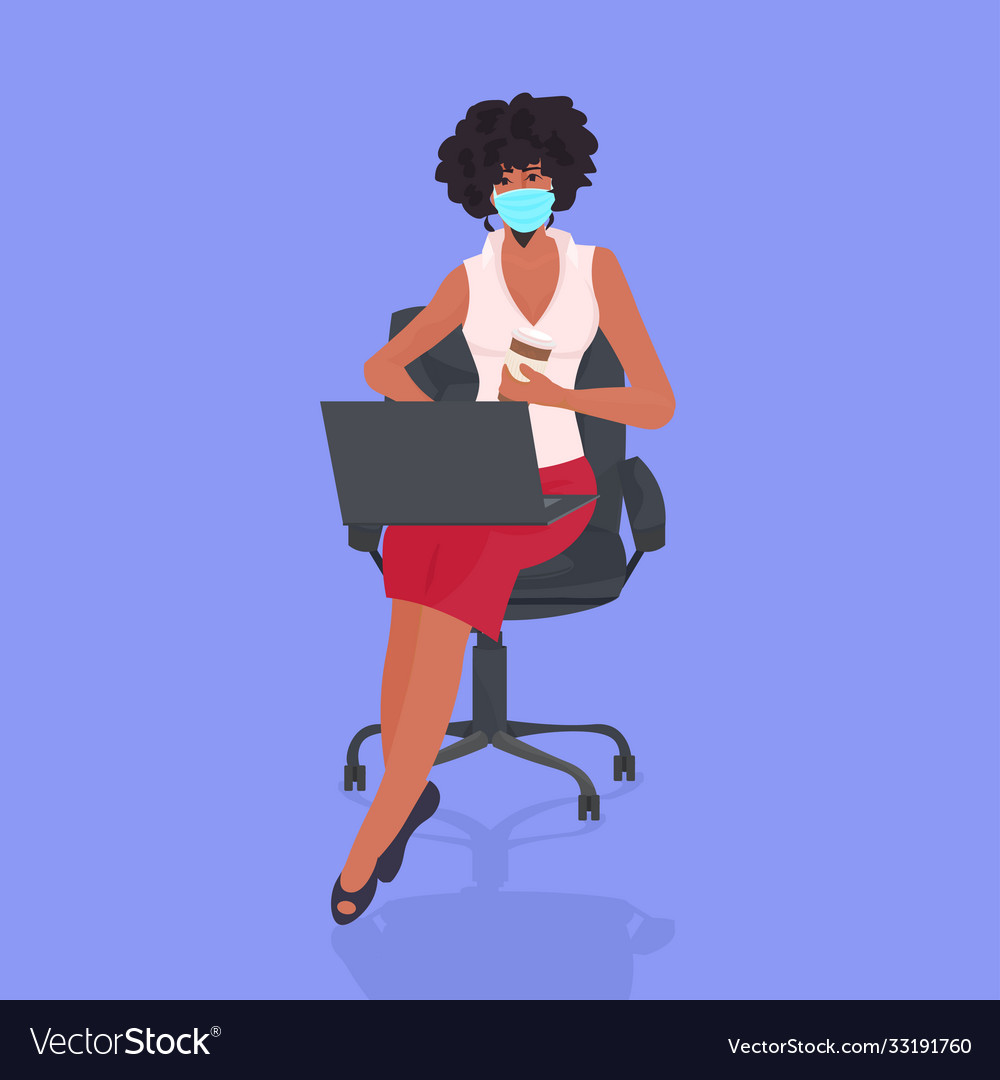 Businesswoman in face mask using laptop