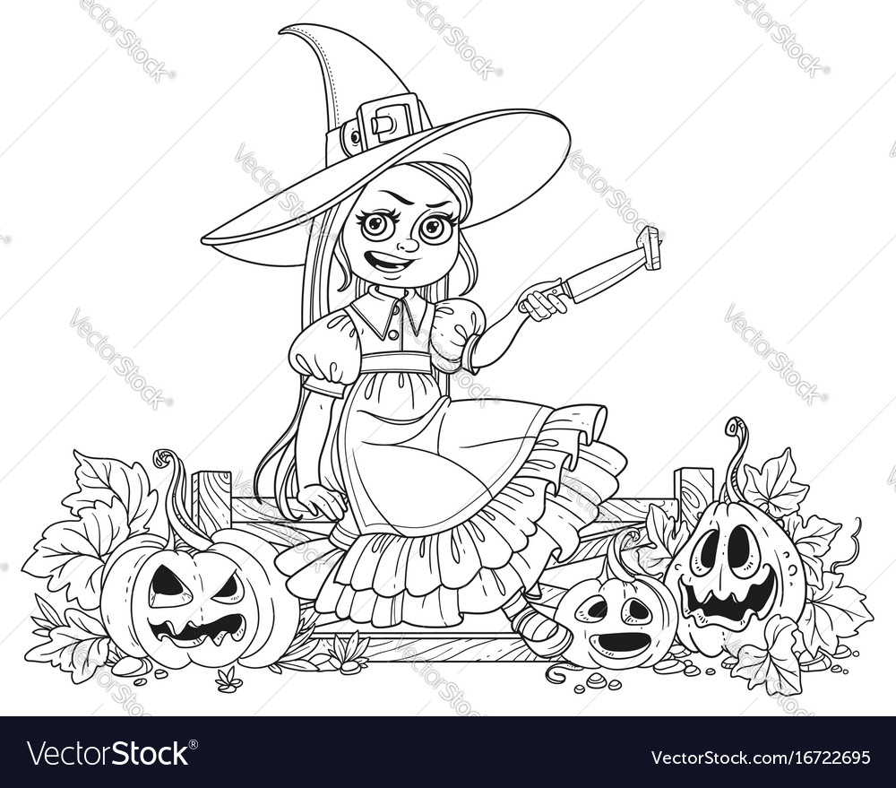 Cute girl in witch costume sitting on the fence