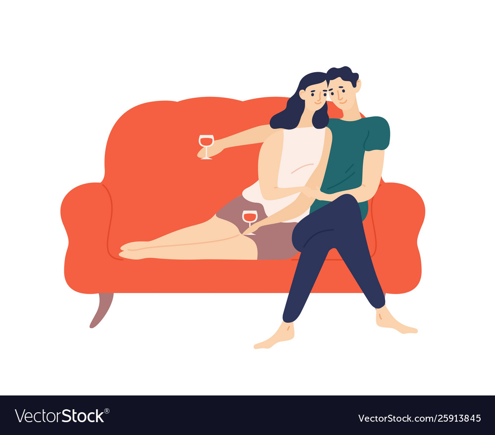 Cute couple sitting on sofa and drinking wine
