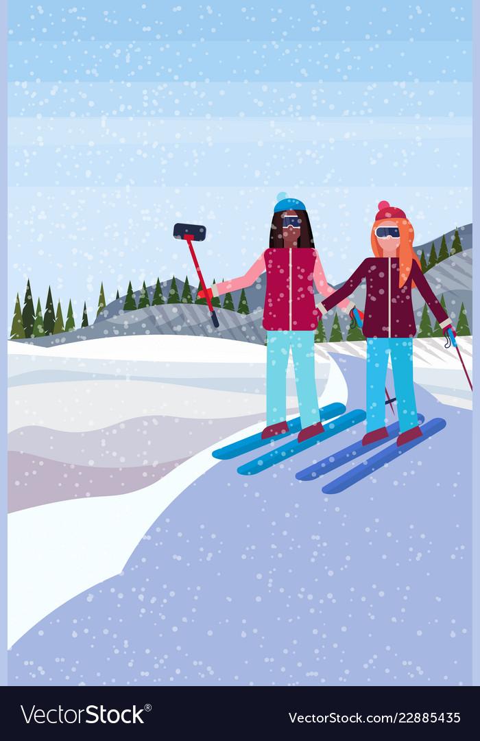 Women couple skiers taking selfie winter snowy