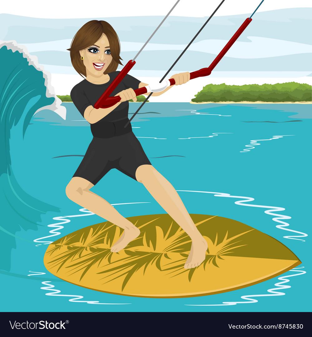 Female kiteboarder enjoys surfing waves