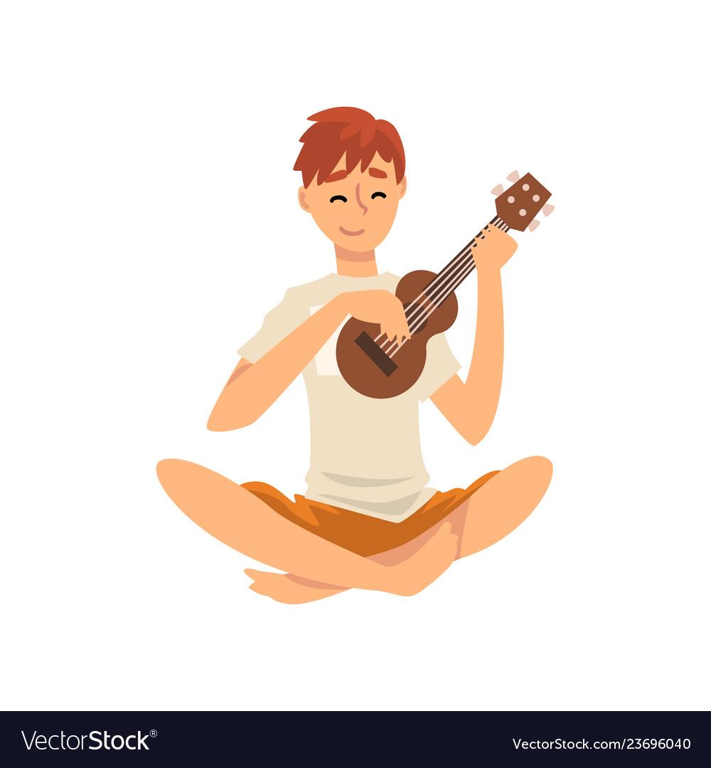 Young man sitting on floor and playing ukulele