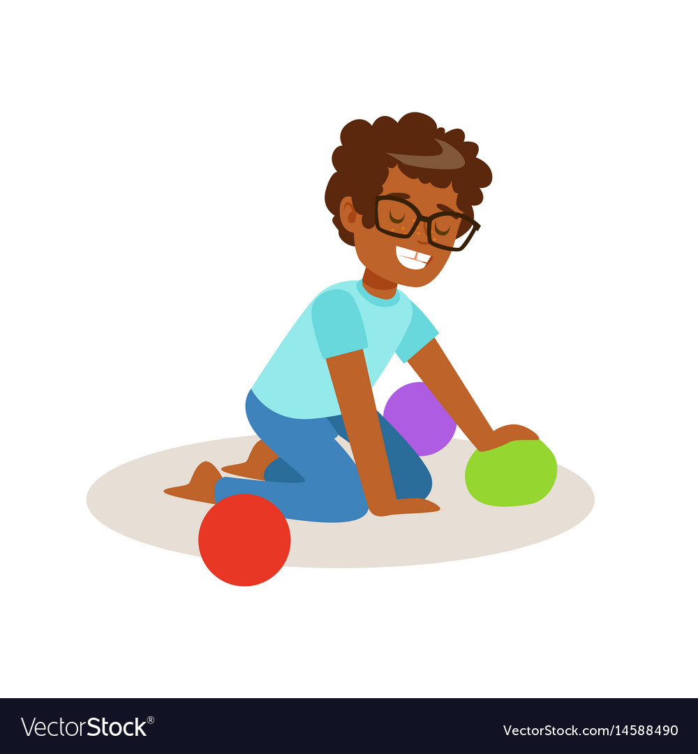 Little boy sitting and playing with colorful balls