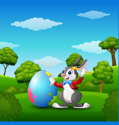 Cartoon easter bunny painting easter eggs in the p vector