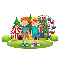 Two boys in front of the carnival vector image
