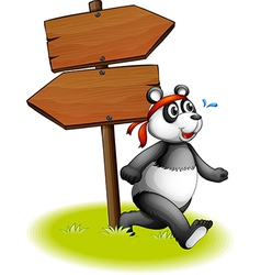 A panda beside the wooden arrowboards vector image