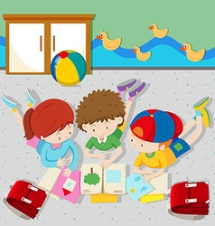 Children reading books in the classroom vector image