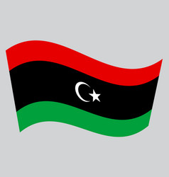 Flag of libya waving on gray background vector