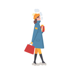 Young woman in winter clothing walking with gift vector