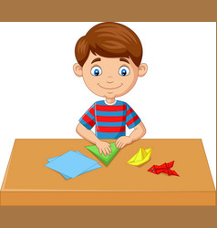 Little boy folding paper and making origami toys vector