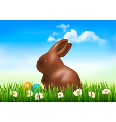 Chocolate bunny with easter eggs in grass vector image
