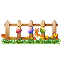 Easter eggs at the fence and a bunny vector image