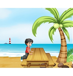 A boy at the beach with a wooden table near the vector image vector image