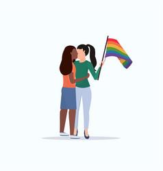women couple holding rainbow flag girls kissing vector image