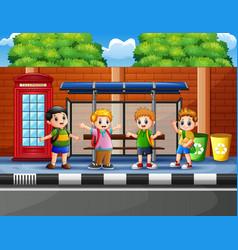 happy school children at the bus stop vector image