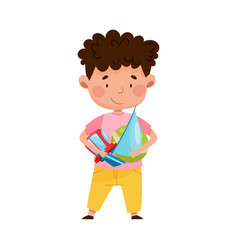 Red cheeked boy holding pile different toys in vector