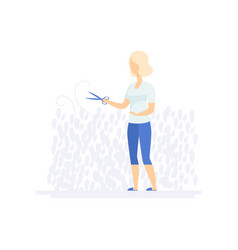 Young woman trimming bushes tree with clippers vector