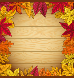 Border from autumn leaves on wooden background vector