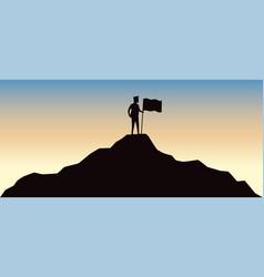 Man holding flag on top mountain vector