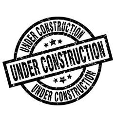 Under construction round grunge black stamp vector