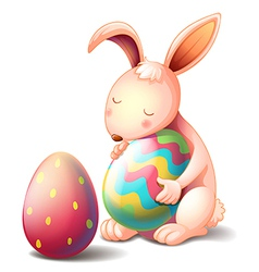 A rabbit hugging a colorful easter egg vector image vector image