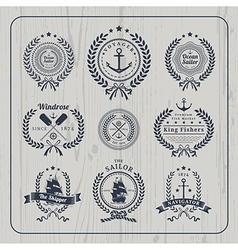 Vintage nautical wreath labels set on light wood vector image