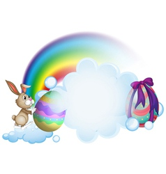 A bunny and the easter eggs near the rainbow vector image vector image