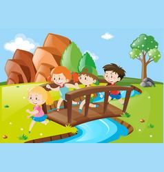 many children crossing bridge in park vector image vector image