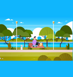 Young guy in park using laptop computer outdoors vector