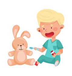 Careful little boy in medical wear treating toy vector