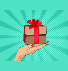 gift box in hand with red bow and ribbons vector image vector image