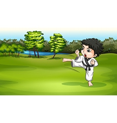 A young boy practicing karate near the river vector image