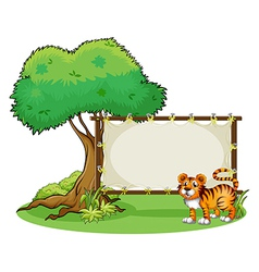 A tiger beside a wooden frame near a big tree vector image vector image