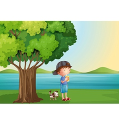 A young boy and his pet under the tree vector