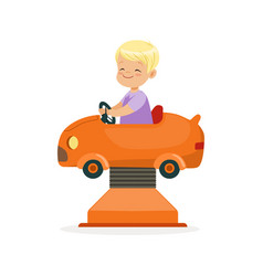 Cute blonde little boy riding on an orange car vector