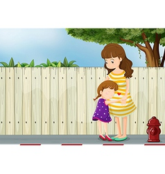 A mother and her daughter near the fence at the vector image vector image