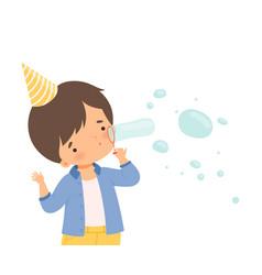 Little boy wearing birthday hat blowing bubbles vector