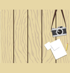 Retro camera and paper on wooden background vector