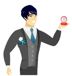 Young asian groom holding wedding ring in box vector