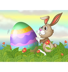 A rabbit and a large egg in the garden vector image