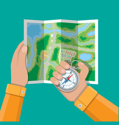 Folded paper city map and compass in hands vector