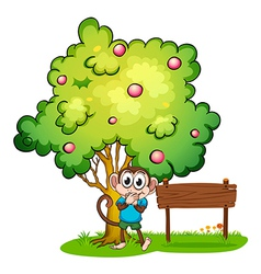 A monkey and an empty signboard under the tree vector image vector image