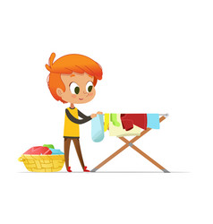 Adorable little redhead boy hanging washed clothes vector