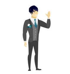 Young asian groom waving his hand vector