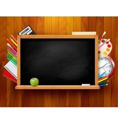 Blackboard with school supplies on wooden vector image vector image