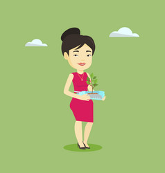 woman holding plant growing in plastic bottle vector image