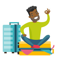 young african-american man sitting on suitcase vector image